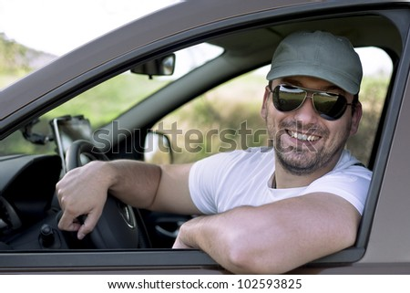 Happy male driver smiling while sitting in a car with open front window. Selective focus.