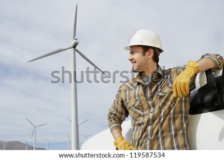 Happy male engineer looking away at wind farm
