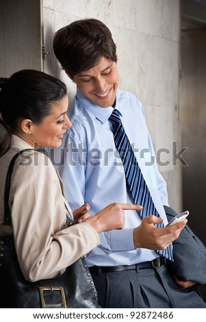 Happy male executive sharing text message on mobile phone with female colleague