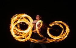 Happy male fire dancer twirl burning baton creating sparkling trails in motion dark outdoors, twirler