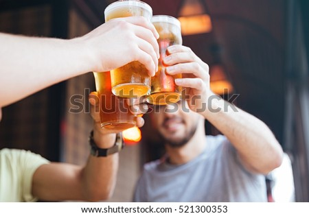 Happy male friends clinking with beer mugs in pub #521300353