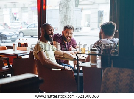 Happy male friends talking in beer pub
