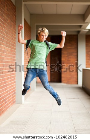 happy male high school student jumping up in school