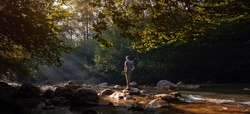 Happy male hiker trekking outdoors in forest near river. idea and concept of adventure, discovery and travel