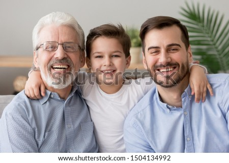 Happy male intergenerational 3 three generation men family close up portrait, cute child boy son grandson embracing young grown father and old grandfather laughing bonding looking at camera at home