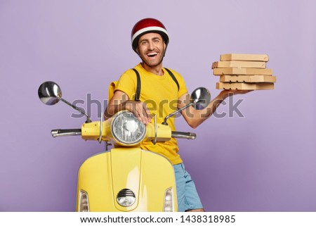 Happy male involved in customer service, picks up pizza, wears helmet, yellow t shirt, carries rucksack, poses near scooter, being energetic and fast, waits for customers near office, transports food #1438318985