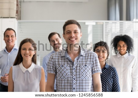 Happy male leader, coach posing with multiracial group of employees, successful business owner with subordinates in office, diverse happy group team staff at background, look at camera