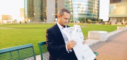 Happy male manager reading newspaper and smiling outside in  . Concept of businessman and mass media. Man dressed in black suit having break.