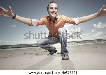 Happy male on the beach smiling and extending his arms