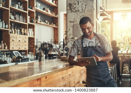 Happy male owner of cafe using digital tablet