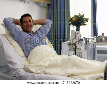 Happy male patient relaxing in hospital bed