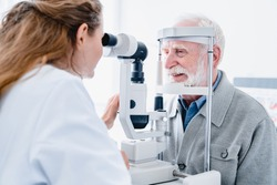 Happy male patient undergoing vision check performed by female ophthalmologist