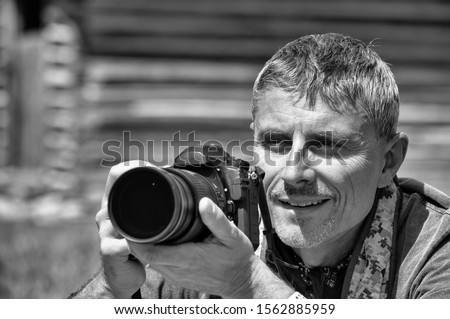 Happy male photographer observing natural landscape before making pictures.