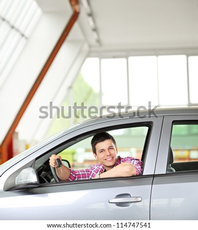 Happy male sitting in his automobile and holding a car key - stock photo
