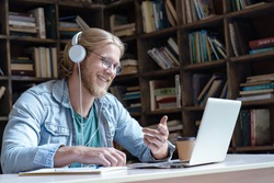 Happy male student online teacher wear headphone talk video calling looking at laptop computer screen do conference chat communicate with skype tutor, distance education e learning course in library