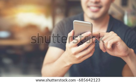 happy male using smartphone at...