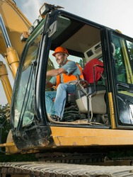 happy male worker operating excavator on construction site
