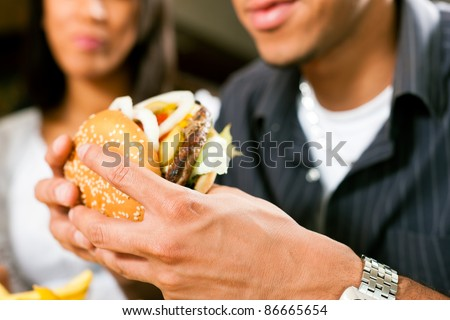 Happy man (African American) in a fast food restaurant eating a hamburger with his girlfriend - stock photo