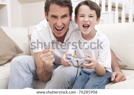 Happy man and boy, father and son, having fun playing video console games together, the young boy has the handset controller while dad is cheering.