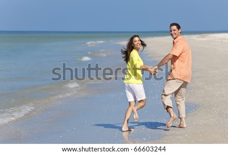 Happy man and woman couple running, laughing and holding hands on a deserted beach with bright clear blue sky