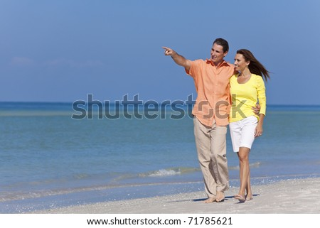 Happy man and woman couple walking and pointing on a deserted beach with bright clear blue sky