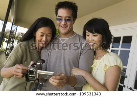 Happy Man and woman looking at video camera screen