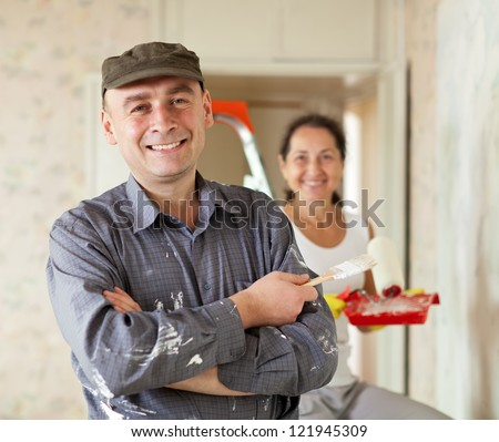Happy man and woman paints wall at home together