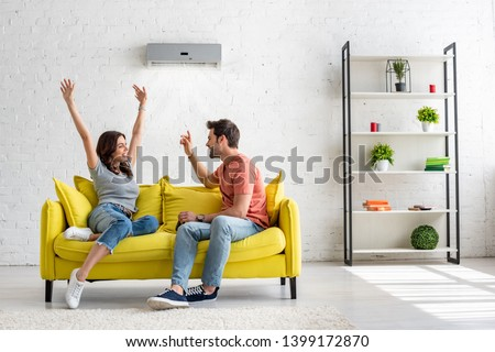 happy man and woman talking while sitting on yellow sofa under air conditioner at home