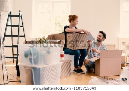 Happy man and woman unpacking stuff from cartoon boxes while furnishing interior #1183915843