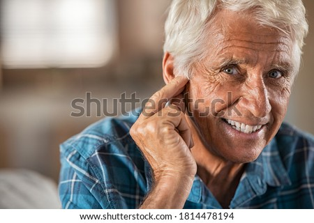 Happy man at home with hearing aid finally hears, copy space. Portrait of smiling senior man holding ear with satisfaction looking at camera. Close up face of old man at home with his new hearing aid. Photo stock ©