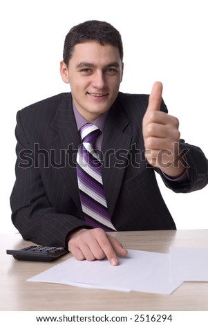 Happy man at the office desk. There are papers and a calculator on the  desk. Isolated on white in studio.