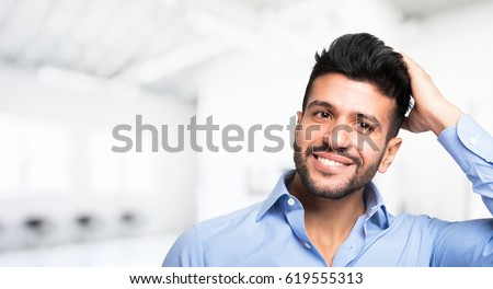Shutterstock Happy man caressing his hair. Large copy-space