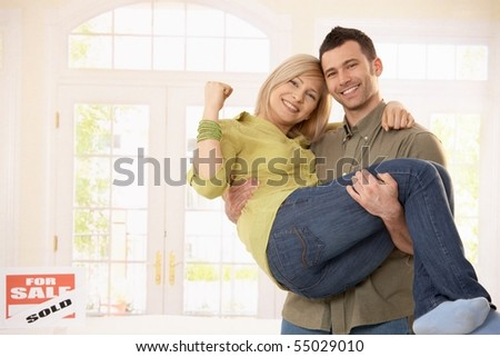 Happy man carrying smiling woman in arms into new home.