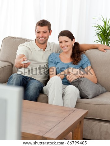 Happy man changing channel while watching television with his wife at home