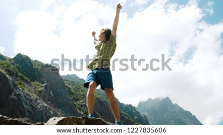 Happy man climbs a boulder and raises his hands up. Bouldering in the mountains #1227835606