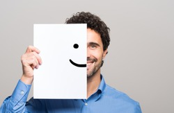 Happy man covering half his face with a smiling emoticon