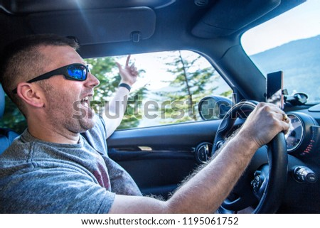 Happy man enjoying a road trip in his car on a sunny day. Singing and listening to music in his car on a scenic drive