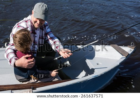 Happy man fishing with his son in the boat #261637571
