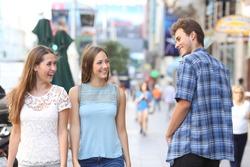 Happy man flirting with tho happy women walking in the street