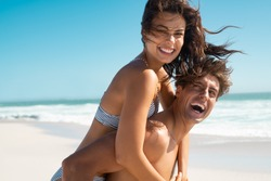 Happy man giving piggyback ride to his woman and laughing at tropical beach. Smiling guy in love carrying on back her girlfriend and having fun. Joyful couple enjoying summer at sea with copy space.