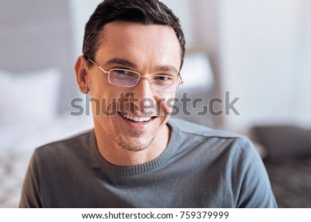 Happy man. Handsome bearded man keeping smile on his face and looking forward while being at home - Shutterstock ID 759379999