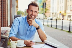 Happy man having coffee break at outdoors cafe during nice summer day