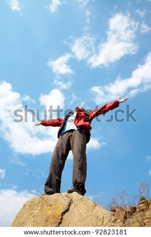Happy man hiker holding his arms in the air in a feeling of success having reached the summit