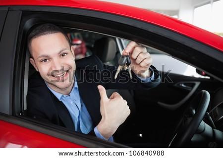 Happy man holding car keys while sitting in a car