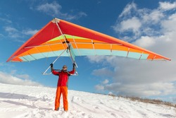 Happy man holding colorful hang glider wing on a slope. Learning to fly