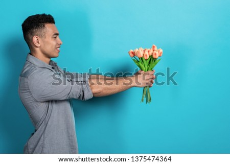 Happy man holding his hands straigth himself with  a tulips bouquet  against a blue studio background .- Image #1375474364