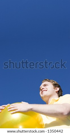 Happy Man holds a big, yellow ball and looks off to the distance under a blue sky