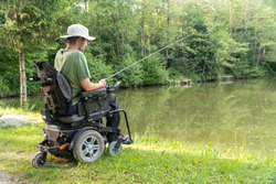 Happy man in a electric wheelchair fishing at the beautiful pond in natue on a sunny day