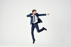 Happy man in a suit jumping up on a light background
