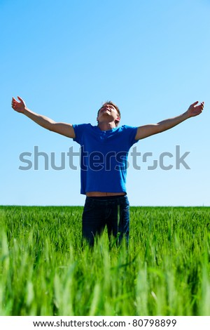 happy man in blue t-shirt standing on green meadow